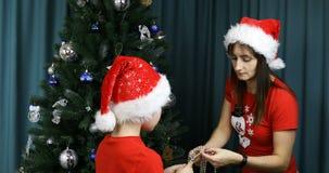 A mãe e o filho desenrolam grânulos do feriado na árvore de Natal filme