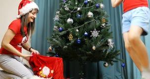 A mãe e o filho ensaiam o papel de Santa Claus com um saco dos presentes video estoque