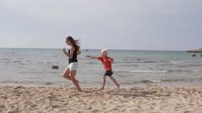 A mãe e o filho estão correndo ao longo do Sandy Beach O filho joga com a mamã em para alcançar no mar video estoque