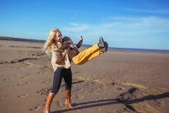 A mãe e o filho estão exultando na praia Foto de Stock Royalty Free