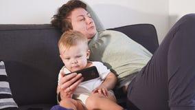 A mãe e o filho estão olhando seus smartphones Conceito do apego do dispositivo video estoque