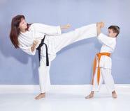 A mãe e o filho estão treinando o pé do pontapé Foto de Stock