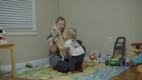 A mãe e o filho jogam com o cão da chihuahua que senta-se no assoalho 4k filme