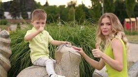 A mãe e o filho pequeno andam no parque no tempo morno do verão, eles polegar das mostras acima vídeos de arquivo