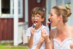 A mãe e o filho que comem a morango endurecem no jardim Imagens de Stock Royalty Free