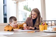 A mãe e o filho tiram lápis coloridos as mãos do desenho Fotografia de Stock Royalty Free