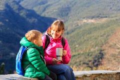 A mãe e o filho viajam nas montanhas que bebem o chá quente Imagens de Stock Royalty Free
