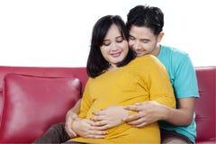 A mãe e o marido grávidos tocam em sua barriga Fotografia de Stock