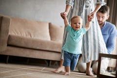 A mãe e o pai aprendem em casa andar seu menino de sorriso da criança fotografia de stock