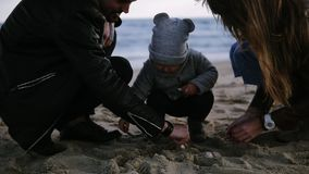 A mãe e o pai com seu menino da criança da criança que joga com a areia no tempo ventoso nebuloso frio, homem ajudam o menino peq video estoque