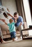 A mãe e o pai de sorriso aprendem em casa andar seu menino da criança foto de stock