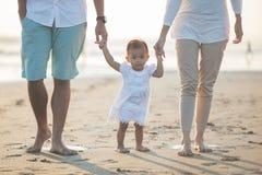 A mãe e o pai estão ensinando suas caminhadas da filha na praia fotos de stock
