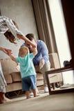 A mãe e o pai felizes aprendem em casa andar seu menino t da criança fotos de stock