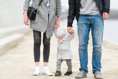 A mãe e o pai guardam a filha pequena pelas mãos Imagens de Stock