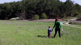 A mãe e o rapaz pequeno vão no campo vídeos de arquivo