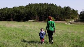 A mãe e o rapaz pequeno vão no campo video estoque