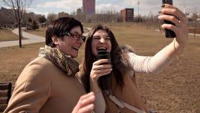 A mãe e os selfies adultos da tomada da filha no parque no verão vão loucos e risos Emoções felizes e positivas pais video estoque