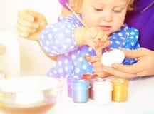Mãe e ovos pequenos da pintura da filha, easter Imagem de Stock