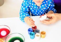 Mãe e ovos pequenos da pintura da filha, easter Imagem de Stock Royalty Free