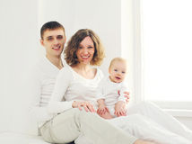 Mãe e pai felizes da família com casa do bebê na sala branca perto da janela Imagens de Stock