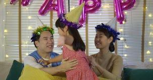 Mãe e pai que beijam sua filha com amor Família feliz que aprecia o tempo junto filme