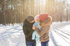Mãe e pai que guardam seu bebê e que beijam sua parte externa no inverno Imagem de Stock