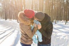Mãe e pai que guardam seu bebê e que beijam sua parte externa no inverno Imagens de Stock Royalty Free