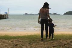 A mãe e pouco seu filho estão guardando a mão no beac Imagem de Stock