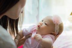 Mãe e riso pequeno do bebê, jogando junto na sala da cama fotografia de stock