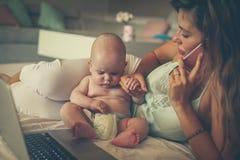 Mãe e seu bebê pequeno em casa Matriz que trabalha em casa fotografia de stock royalty free