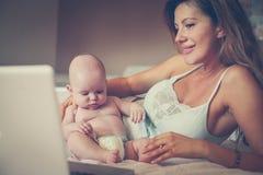 Mãe e seu bebê pequeno em casa Matriz que trabalha em casa fotografia de stock