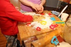 Mãe e seu bebê pequeno que fazem cookies das mãos em casa na cozinha fotos de stock royalty free