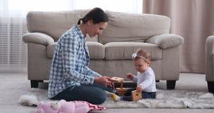 Mãe e seu bebê que jogam com brinquedo em casa vídeos de arquivo