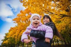 A mãe e seu bebê têm o divertimento no parque do outono Fotos de Stock