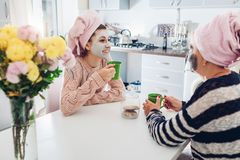 A mãe e seu chá bebendo da filha adulta com máscaras faciais aplicaram-se Mulheres que refrigeram e que falam na cozinha fotografia de stock