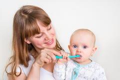 Mãe e seus dentes de escovadela do bebê junto imagem de stock