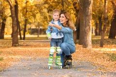 Mãe e seus patins de rolo vestindo da filha fotos de stock royalty free
