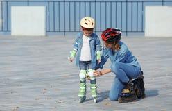 Mãe e seus patins de rolo vestindo da filha imagem de stock