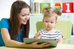 Mãe e sua filha da criança com PC da tabuleta Fotografia de Stock Royalty Free