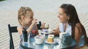 Mãe e sua filha pequena bonito no café exterior filme
