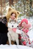 Mãe e sua filha que abraçam cães de puxar trenós Fotografia de Stock
