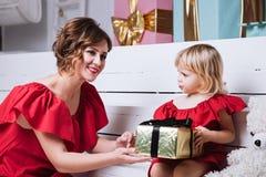 Mãe e sua filha que trocam presentes do Natal foto de stock