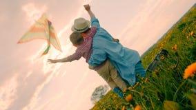 A mãe e suas crianças pequenas estão olhando o papagaio do voo na luz do por do sol no campo Imagem de Stock