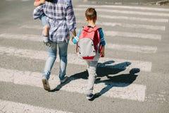Mãe e suas crianças que cruzam a estrada Foto de Stock