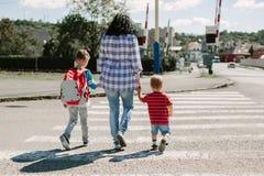 Mãe e suas crianças que cruzam a estrada Fotografia de Stock