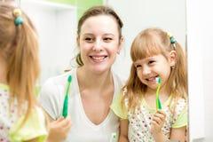 A mãe ensina a menina da criança escovar os dentes imagens de stock