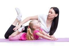A mãe ensina a menina da criança que exercita mostrar perto fotos de stock royalty free