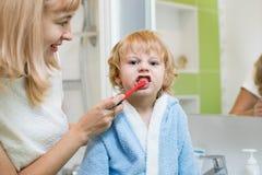 A mãe ensina a seu filho a escova seus dentes no banheiro foto de stock