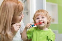 A mãe ensina a seu filho pequeno como escovar os dentes foto de stock