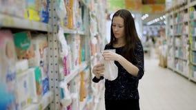 A mãe escolhe o tecido para seu interior da criança do mercado, tecidos seletos do bebê da jovem mulher no supermercado e vídeos de arquivo